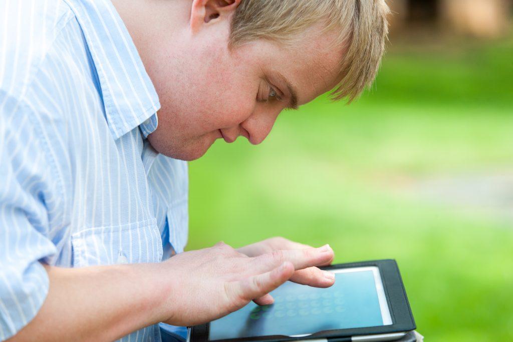 Foto de perfil de um jovem branco com cabelos loiros em ambiente externo. Ele olha atentamente para um tablet e toca a tela com seus dedos.