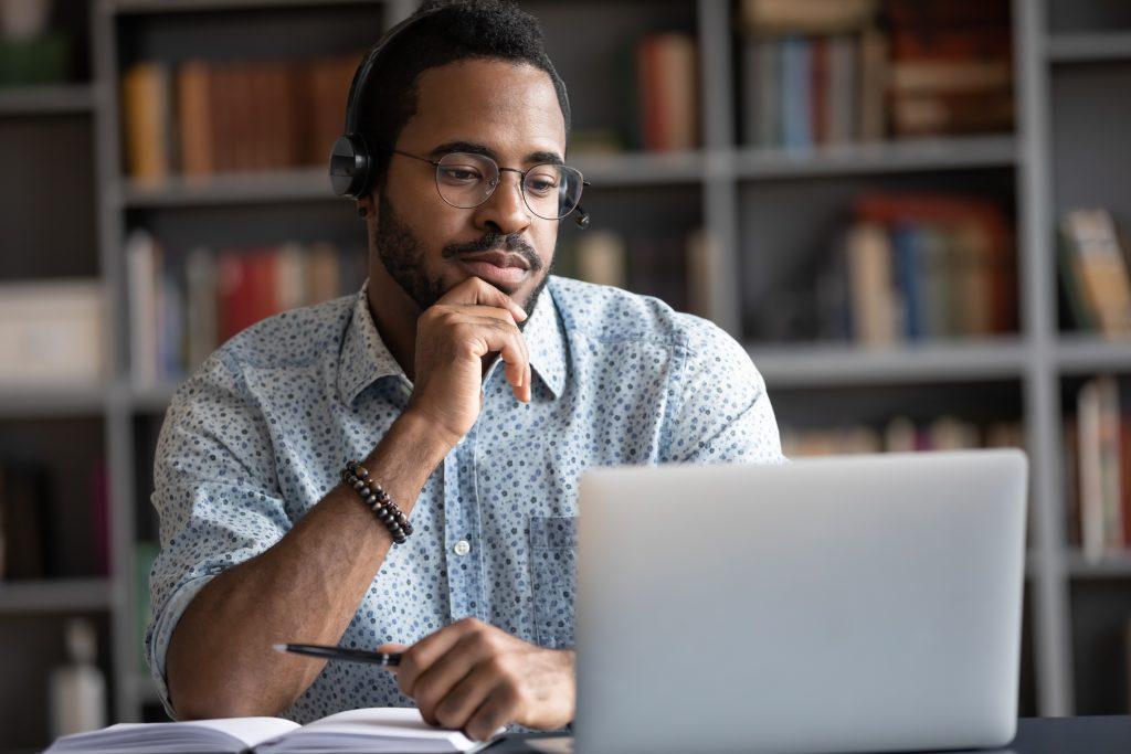Foto de homem negro em sala com estante de livros ao fundo. Ele apoia os braços sobre a mesa e olha para a tela do notebook à sua frente.